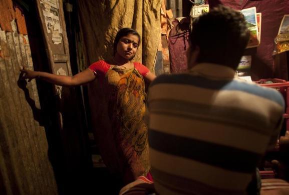 Hashi talks with a customer at Kandapara brothel in Tangail