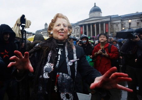 A woman wearing mask representing late former British PM Thatcher poses for photographers at party to celebrate Thatcher's death at Trafalgar Square in London