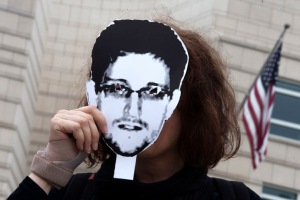 Woman holds a portrait of former U.S. spy agency contractor Snowden in front of her face as she stands in front of the U.S. embassy during a protest in Berlin