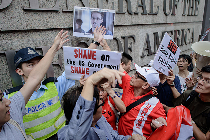Protesters shout slogans as they hold up a picture of former US spy Edward Snowden in front of the US consulate in Hong Kong on June 13, 2013.  Snowden broke his silence on June 12, vowing to fight any bid to extradite him from Hong Kong and accusing Washington's cyber-troops of prying into hundreds of thousands of targets globally including many in China.  AFP PHOTO / Philippe Lopez