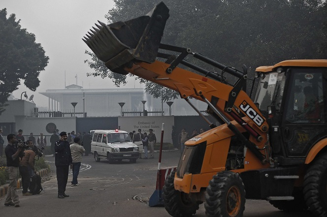A bulldozer removes the security barriers in front of the U.S. embassy in New Delhi December 17, 2013. Indian authorities removed security barriers in front of the U.S. embassy in New Delhi on Tuesday apparently in retaliation for the arrest and alleged heavy-handed treatment of an Indian diplomat in New York. New Delhi police used tow trucks and bulldozers to remove the concrete barricades, which are used to restrict traffic on the road outside the embassy