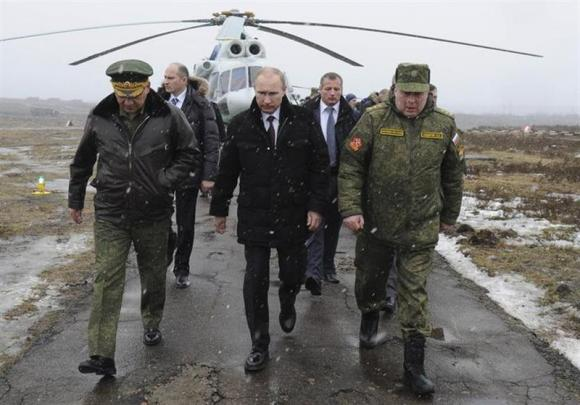 Russia's President Vladimir Putin (front C), accompanied by Russian Defence Minister Sergei Shoigu (front L), walks to watch military exercises upon his arrival at the Kirillovsky firing ground in the Leningrad region, March 3, 2014. REUTERS/Mikhail Klimentyev/RIA Novosti/Kremlin