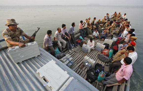 Polling officers with electronic voting machines (EVM) along with Indian security personnel travel in a boat to reach polling stations ahead of the sixth phase of the general election in Assam April 23, 2014. REUTERS/Utpal Baruah