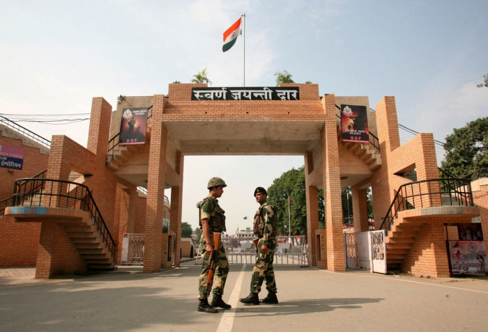 India's Border Security Force (BSF) soldiers patrol in front of the golden jubilee gate at the Wagah border, on the outskirts of the northern Indian city of Amritsar, November 3, 2014. India and Pakistan have suspended a daily military ritual on their main land border crossing after a suicide attack that killed dozens of people, the first time the colorful parade has been called off since the two countries went to war in 1971. India's home ministry said BSF agreed to a Pakistani request to suspend the flag-lowering ceremony to allow mourning. At least 45 people were killed and more than 100 wounded on Sunday by the explosion that ripped through a carpark about 500 meters (yards) from Pakistan's border gate just as hundreds of people left the popular daily performance. REUTERS/Munish Sharma (INDIA - Tags: POLITICS CIVIL UNREST MILITARY TPX IMAGES OF THE DAY) - RTR4CLI5