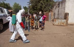 Nov. 14, 2014, a health A health worker sprays disinfectant near a mosque, Mali
